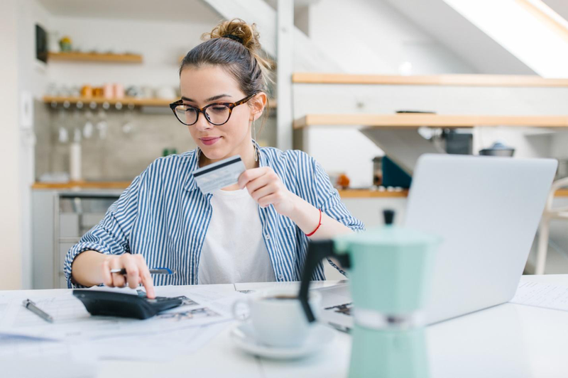 woman sitting at table with laptop, credit card, calculator, and coffee