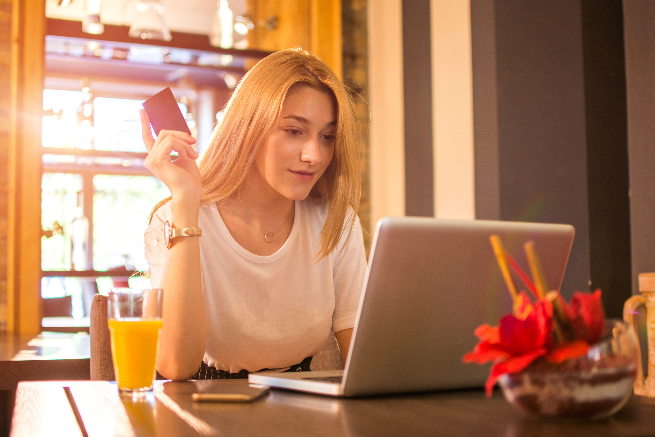 Young adult woman at laptop holding credit card.