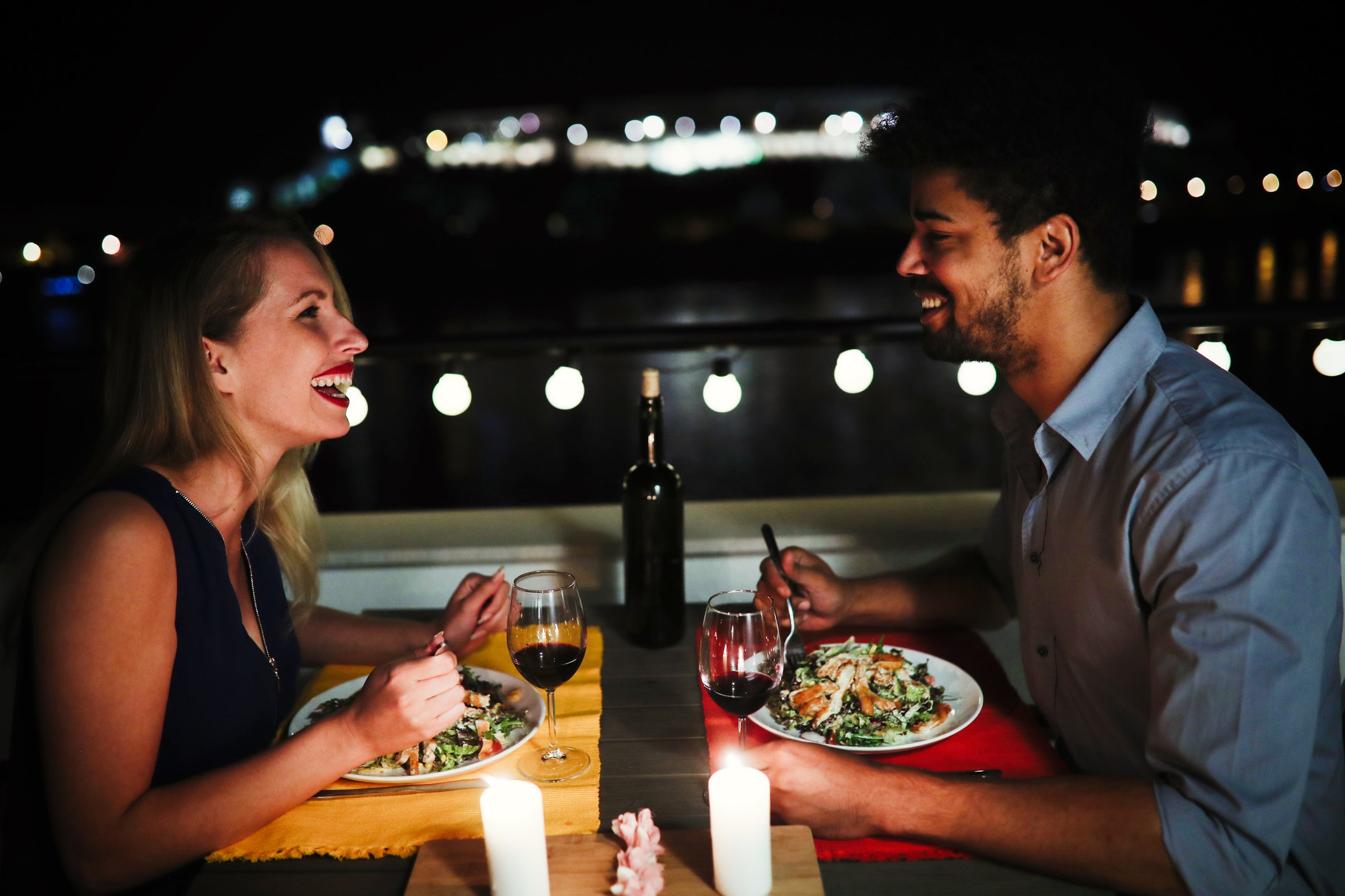 young man and woman sitting at table eating dinner and laughing