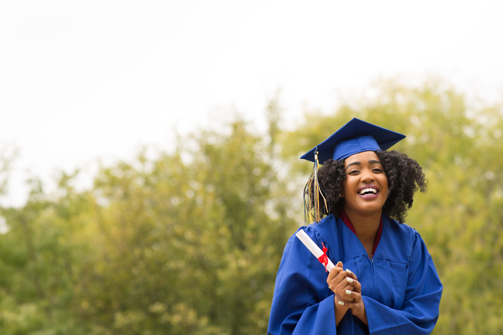 young smiling woman on graduation day wearing robe and mortarboard and holding diploma