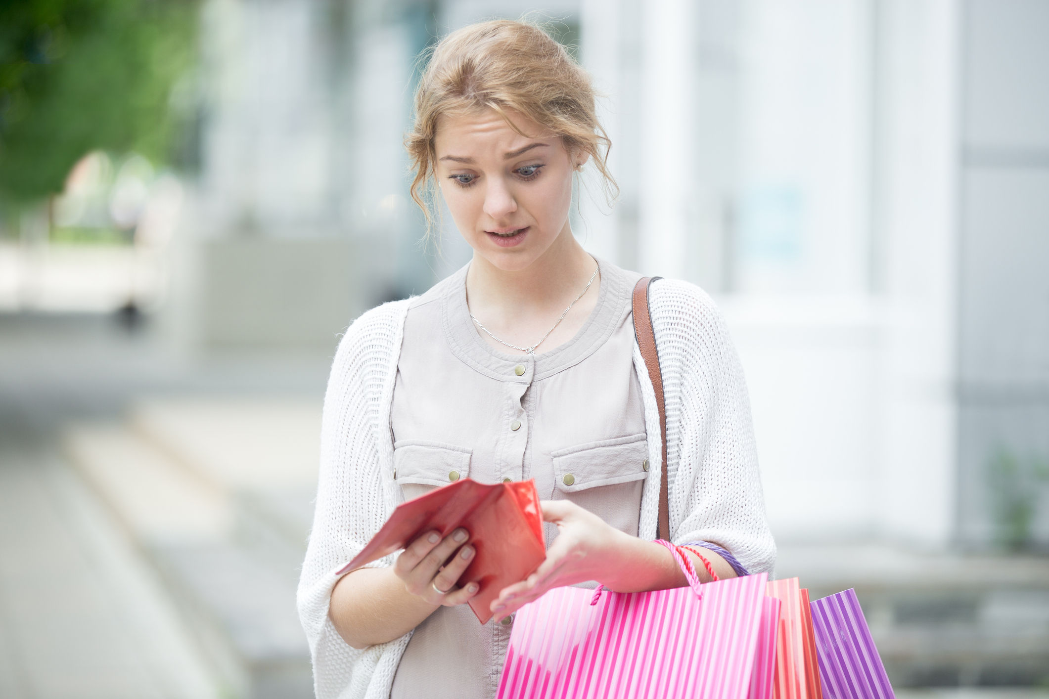 Young woman carrying shopping bags and looking into wallet with concern.